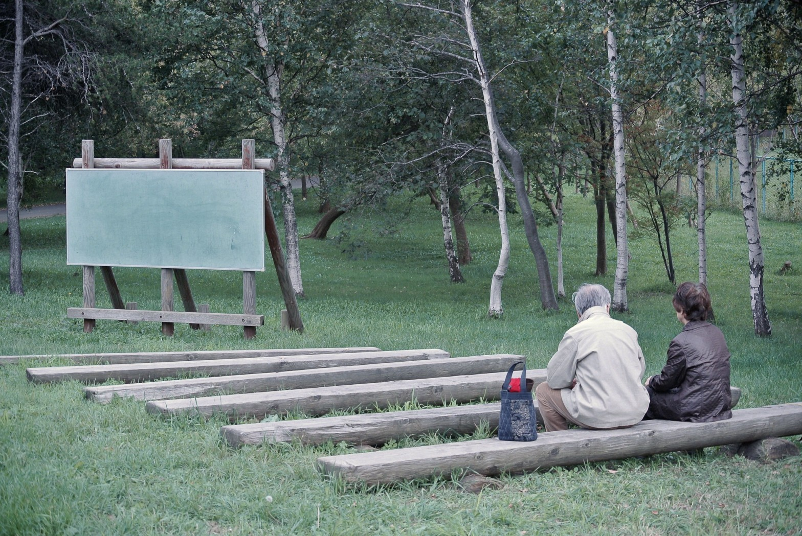 Image of two people sitting at an outdoor classroom